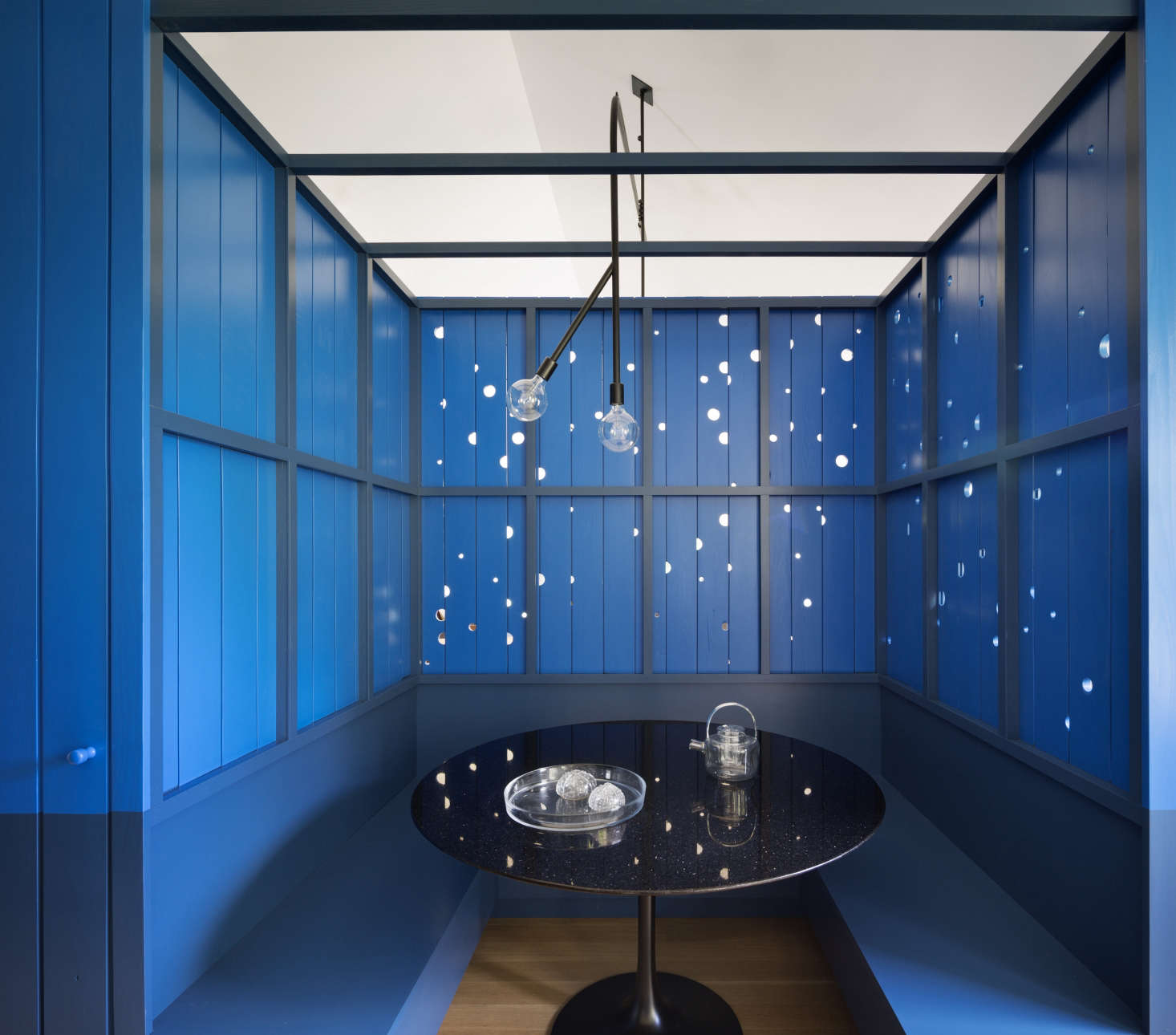 Dramatic blue banquette (with holes in the wood panels that allow in natural light), a design by O'Neill Rose Architects