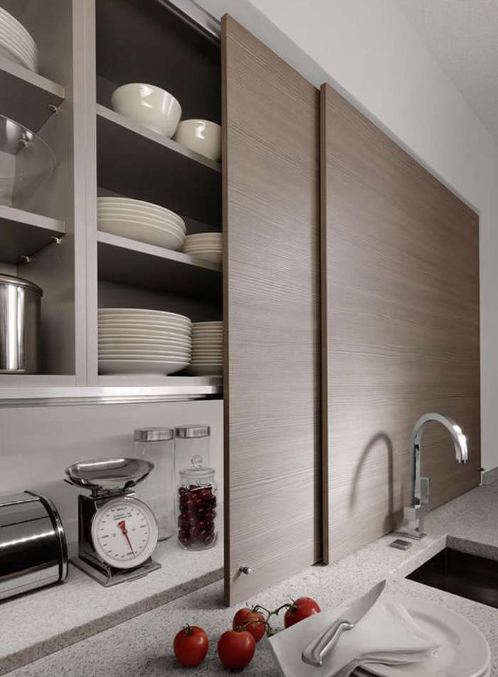 Thin sliding cabinet doors in a kitchen by Germany company Beeck Kuchen conceal countertop clutter.