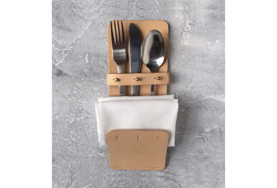 A Cutlery – Pocket made of vegetable-tanned leather and brass buttons holds silverware and a napkin; 480 DKK (about $75) from MO Denmark. For more from the designers, see our post Vegetable-Tanned Leather Goods from MO Denmark.