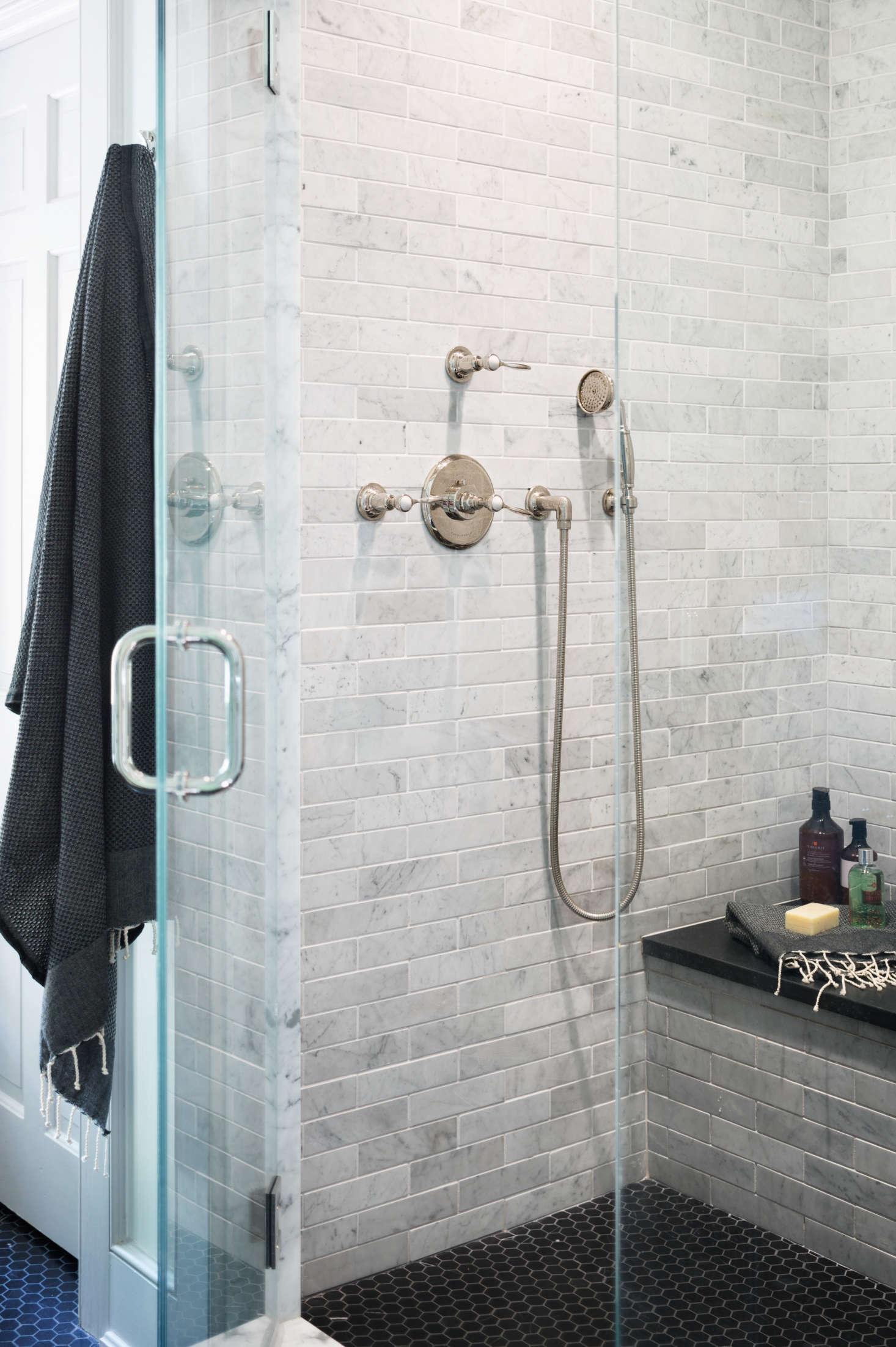 marble-tile-shower-in-modern-farmhouse-renovation-black-hex-tile-floor