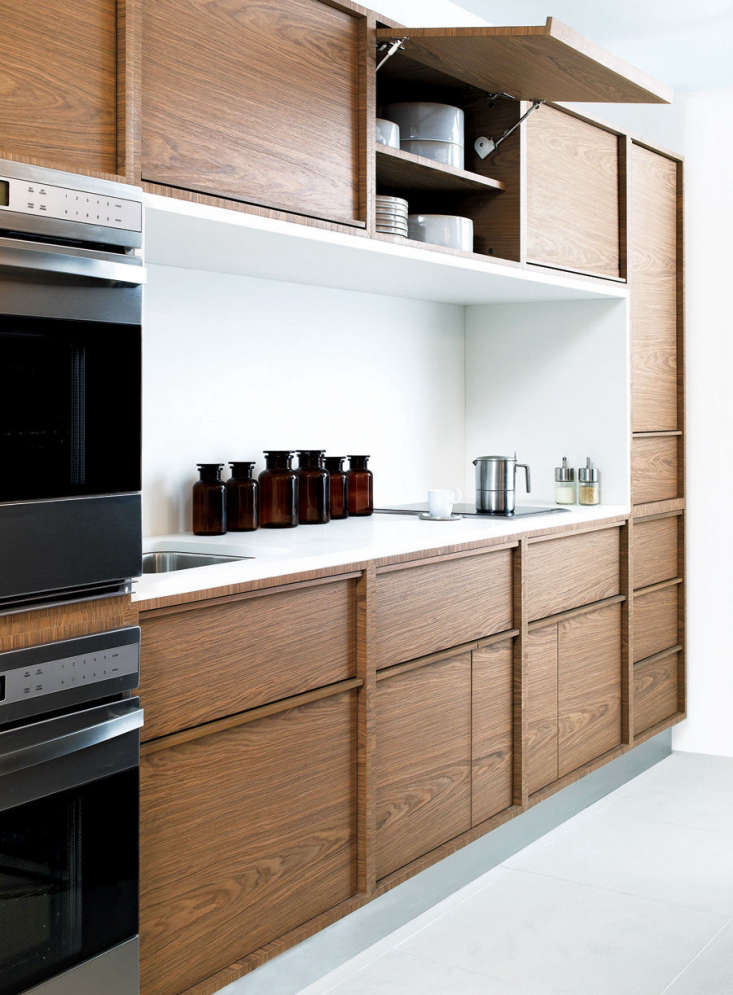 Garage door hinges for upper cabinets allow for easy access in a kitchen by San Francisco–based Nilus Designsfor DWR. (Unfortunately, they are no longer available.)