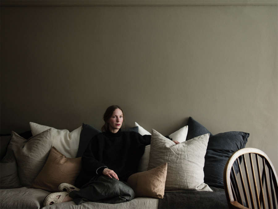 Amy Revier sitting on sofa comprised of soft colored linen cushions