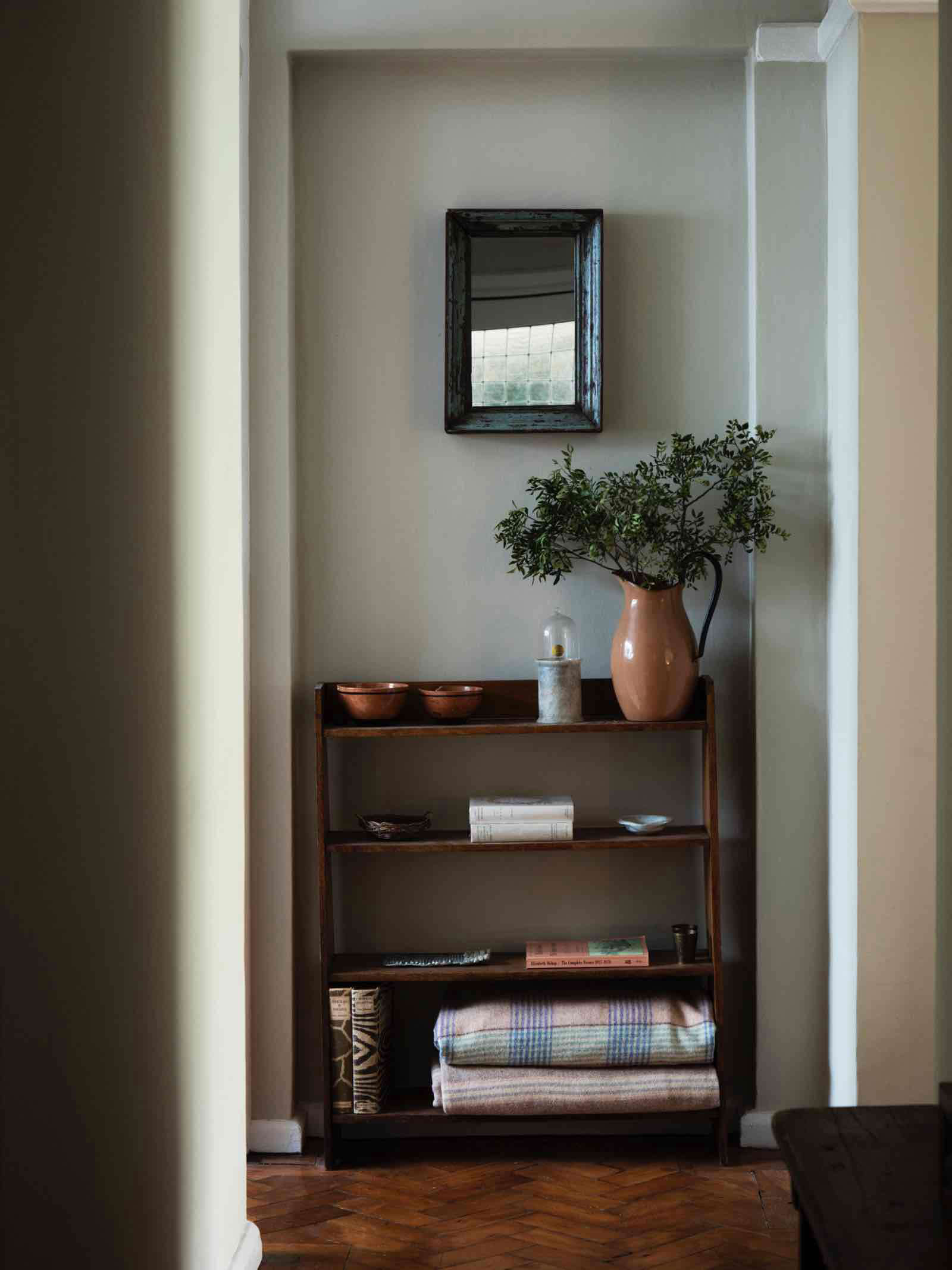 hall way with bookshelf with terracotta bowls and welsh blankets 17