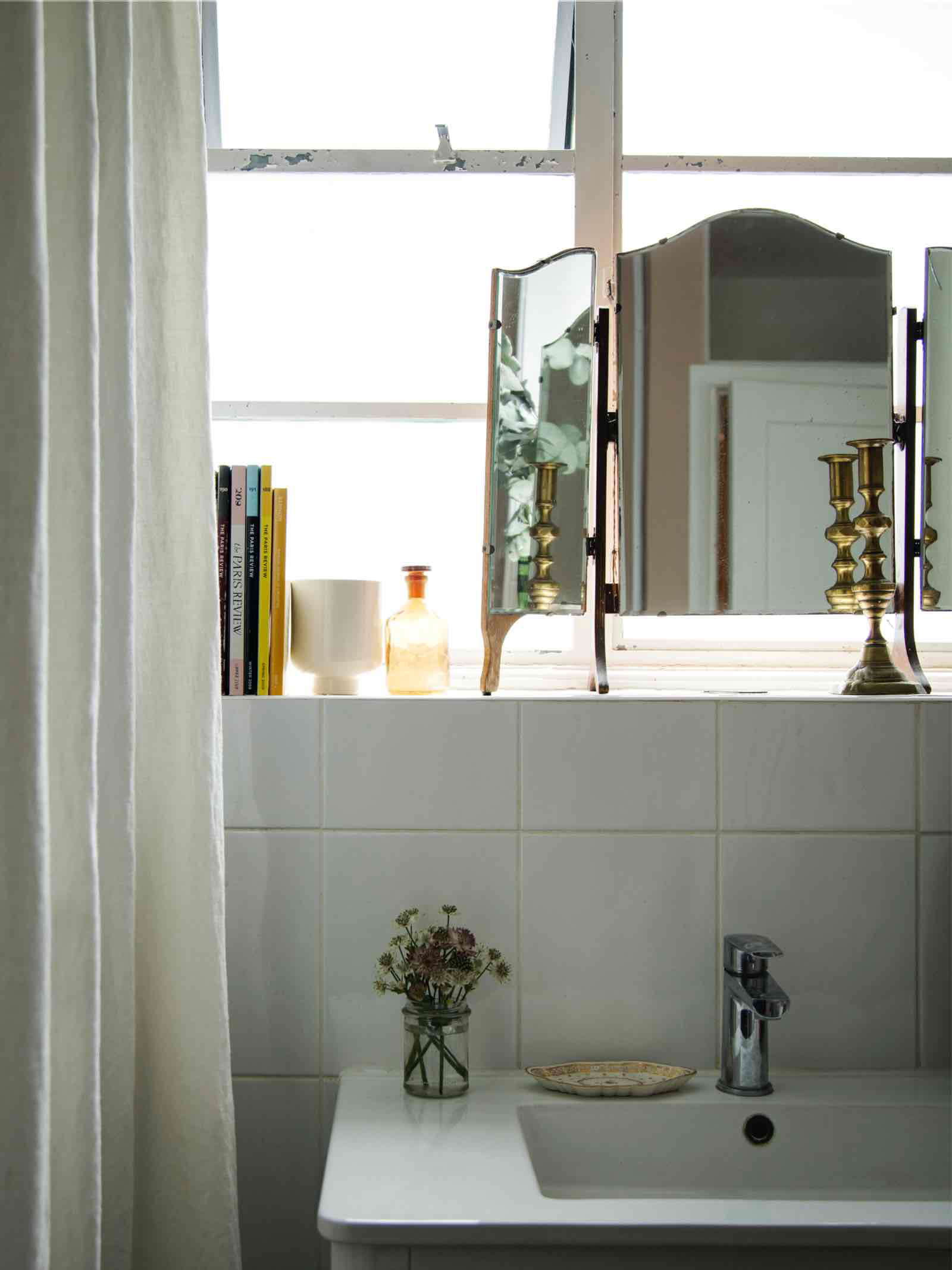 bathroom ledge with free standing mirror and brass candlestick