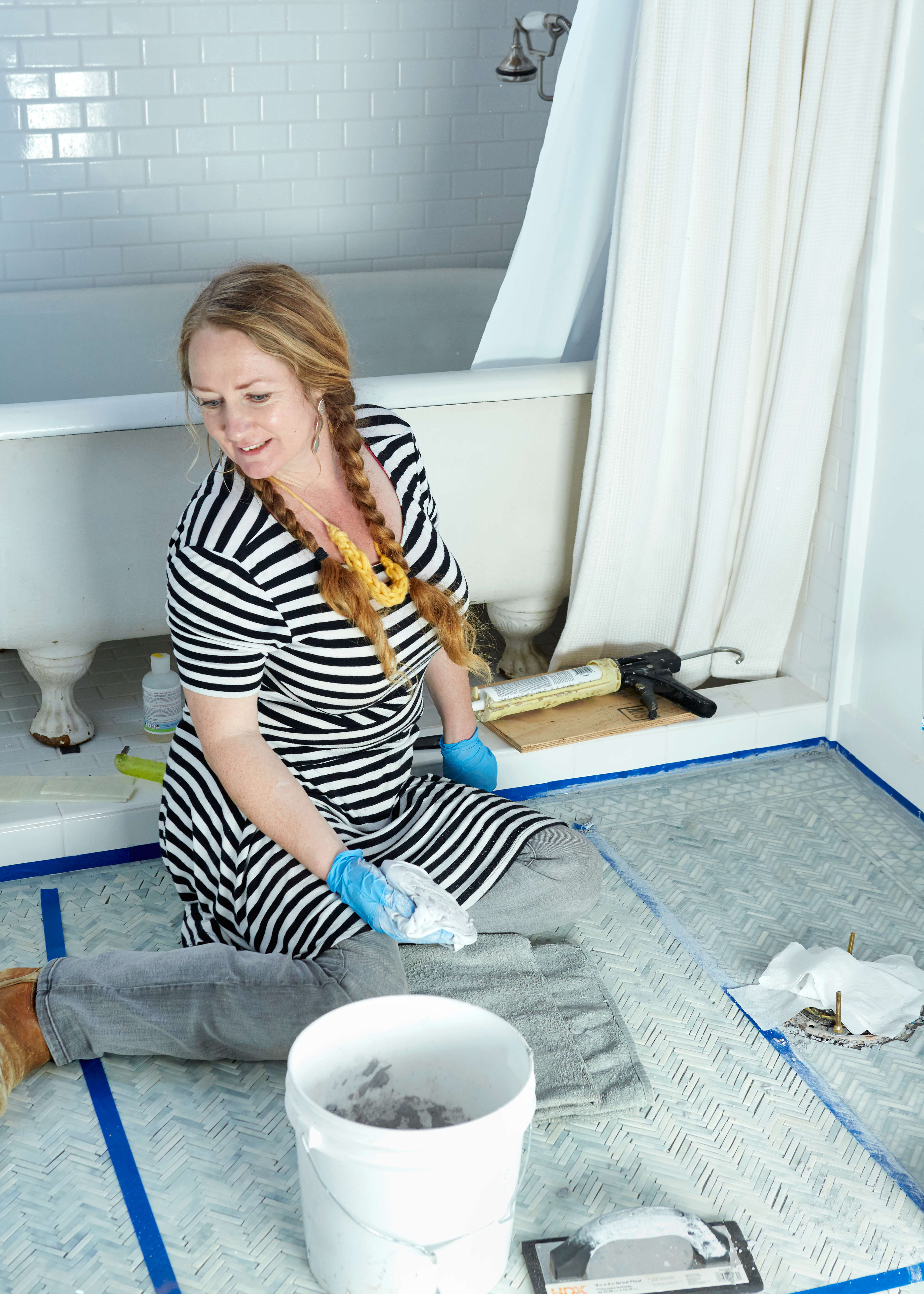 Once the tile is taped into place, Myers works section by section applying sanded grout—&#8