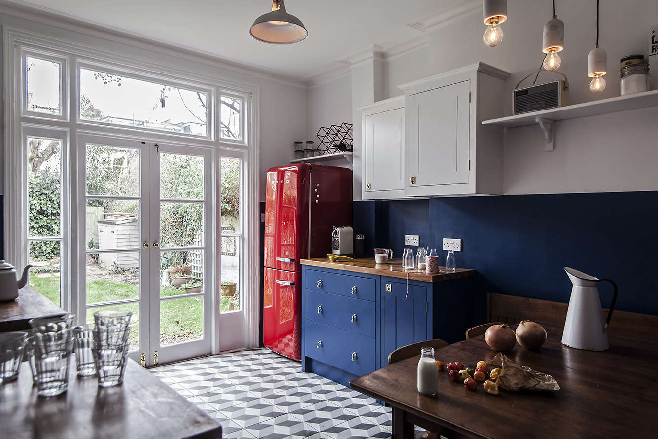 Colorful kitchen remodel in London with a red Smeg refrigerator and blue British Standard cabinets
