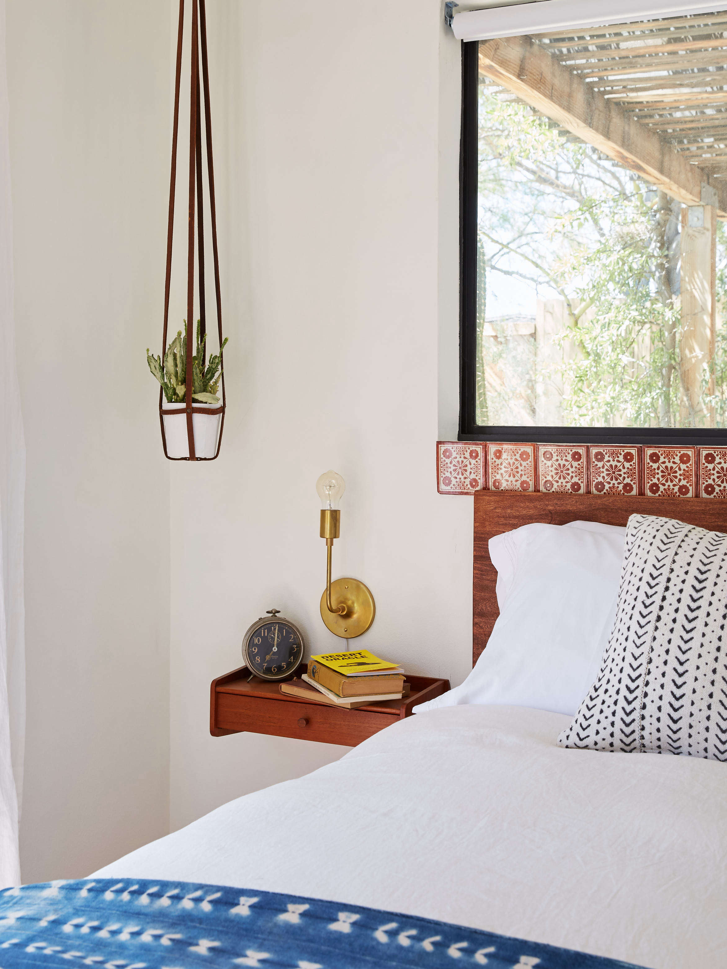 joshua tree casita airbnb bedroom with hanging wood sidetables and tiled headboard/window ledge, kate sears photo