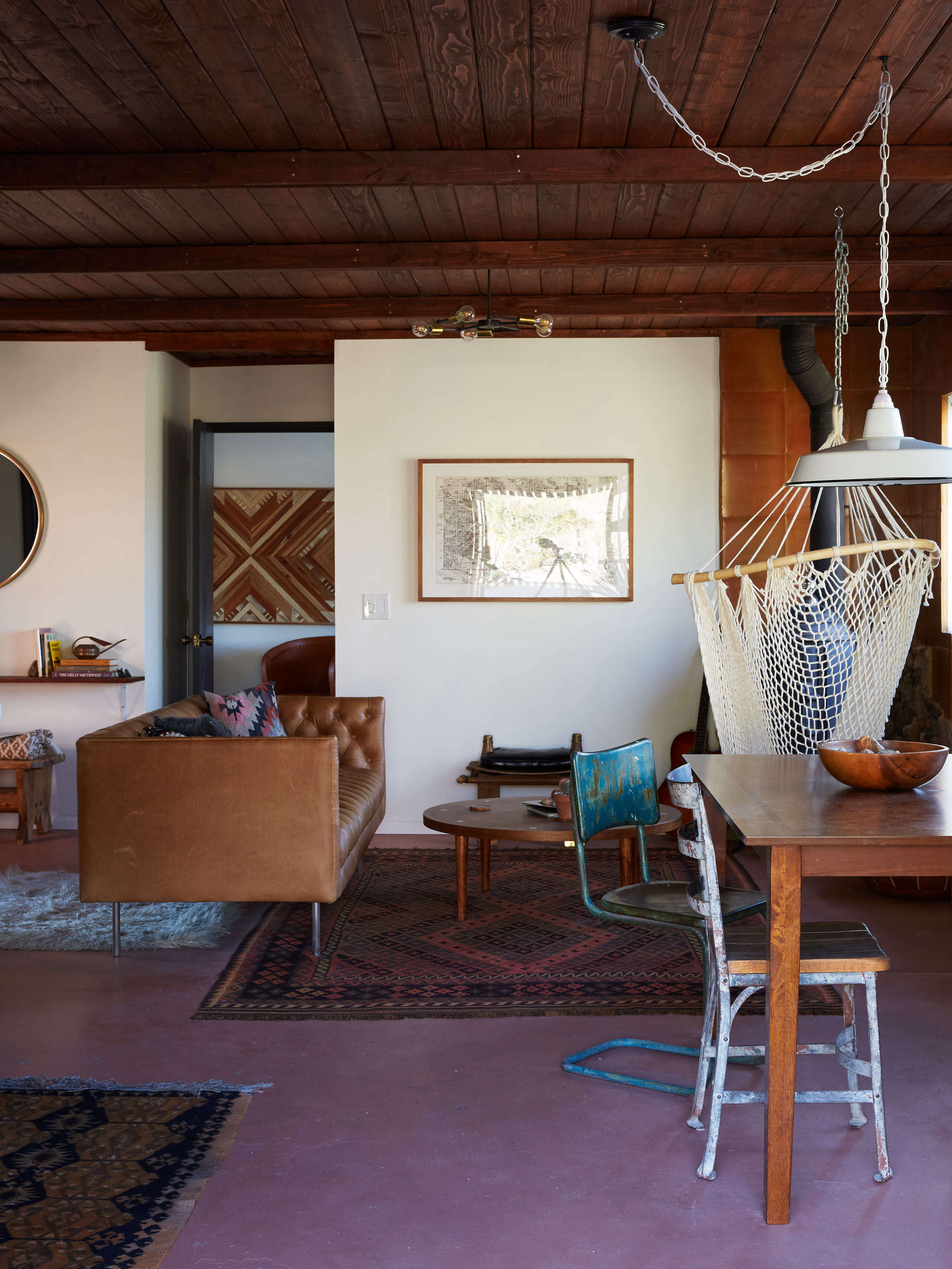 joshua tree casita airbnb living room in desert colors with hanging swing and painted concrete floor, kate sears photo