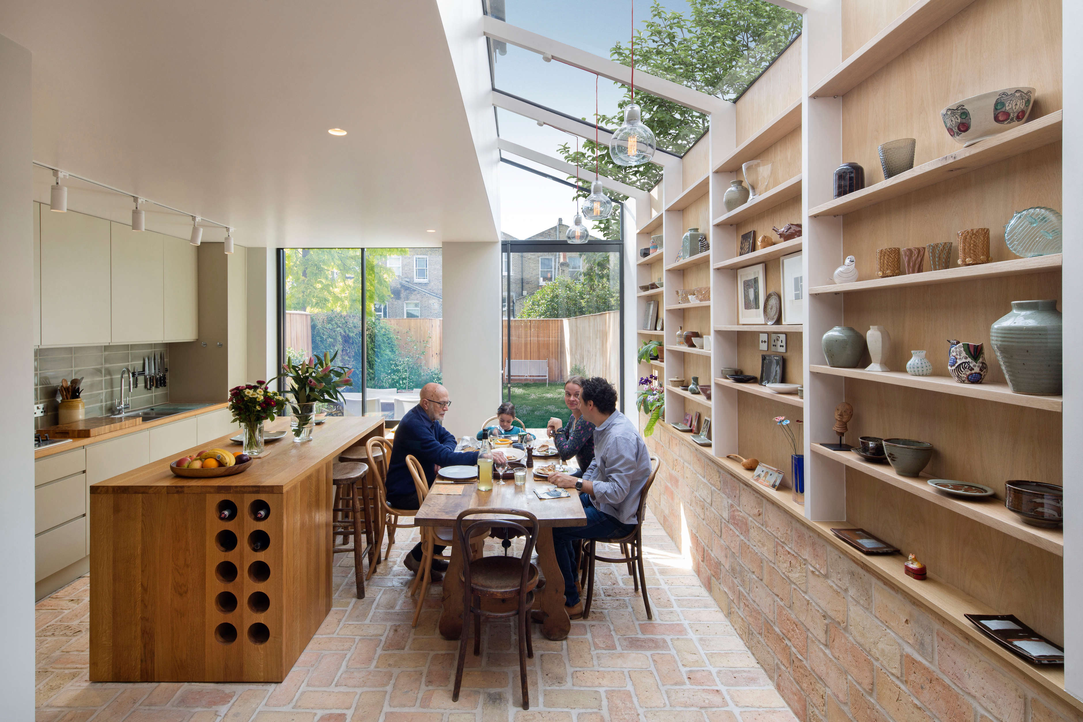 an island with built in wine bottle storage neatly divides the dining area from 11