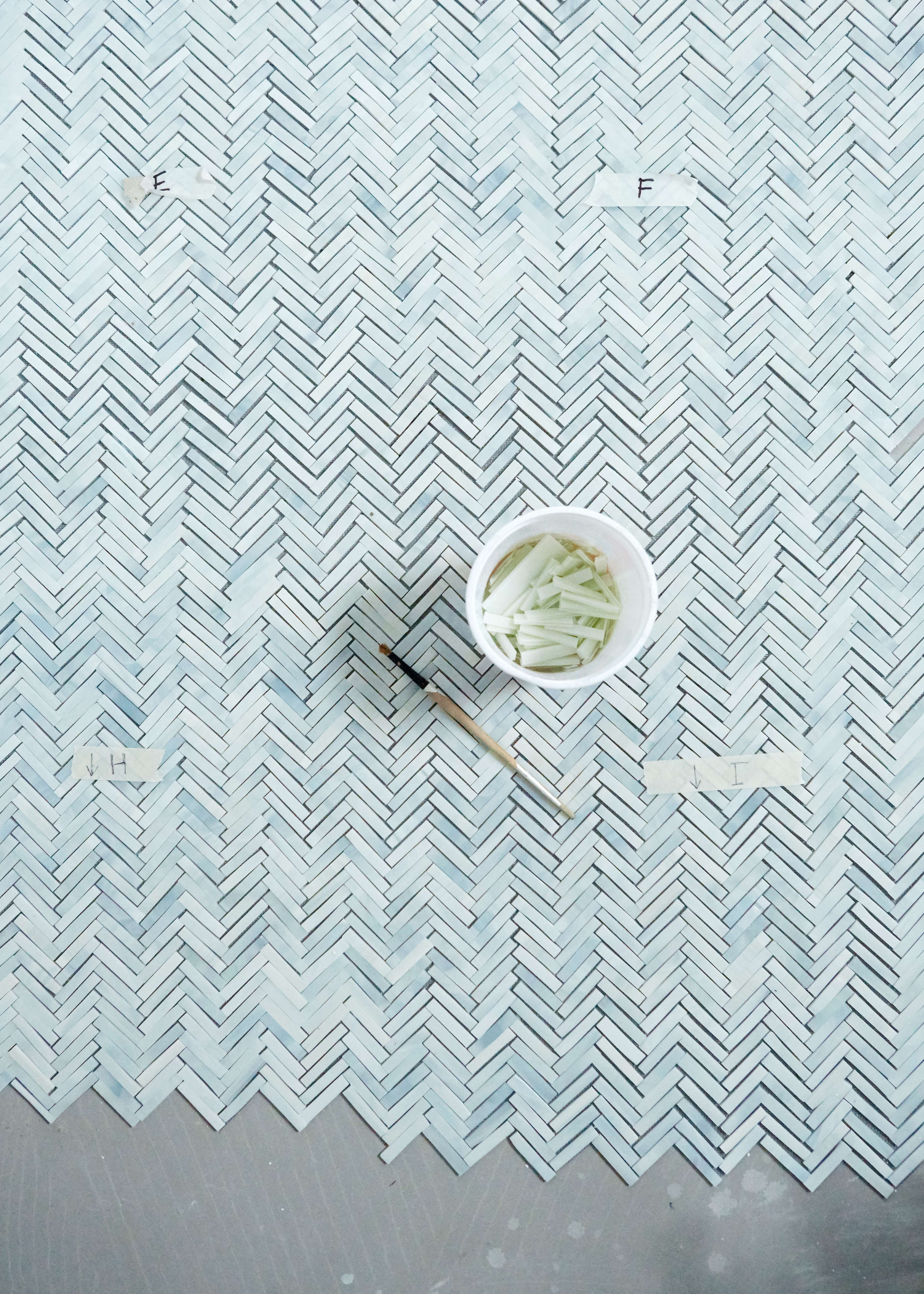 Myers uses a no-VOC industrial adhesive by Eco-Bond to adhere the tesserae to the mesh. Laying the tiles on the concrete mortar bed is what brings out the foggy blue variationsin the opal glass. After the tiles are cut, Myers notes that she mixes up the pieces &#8
