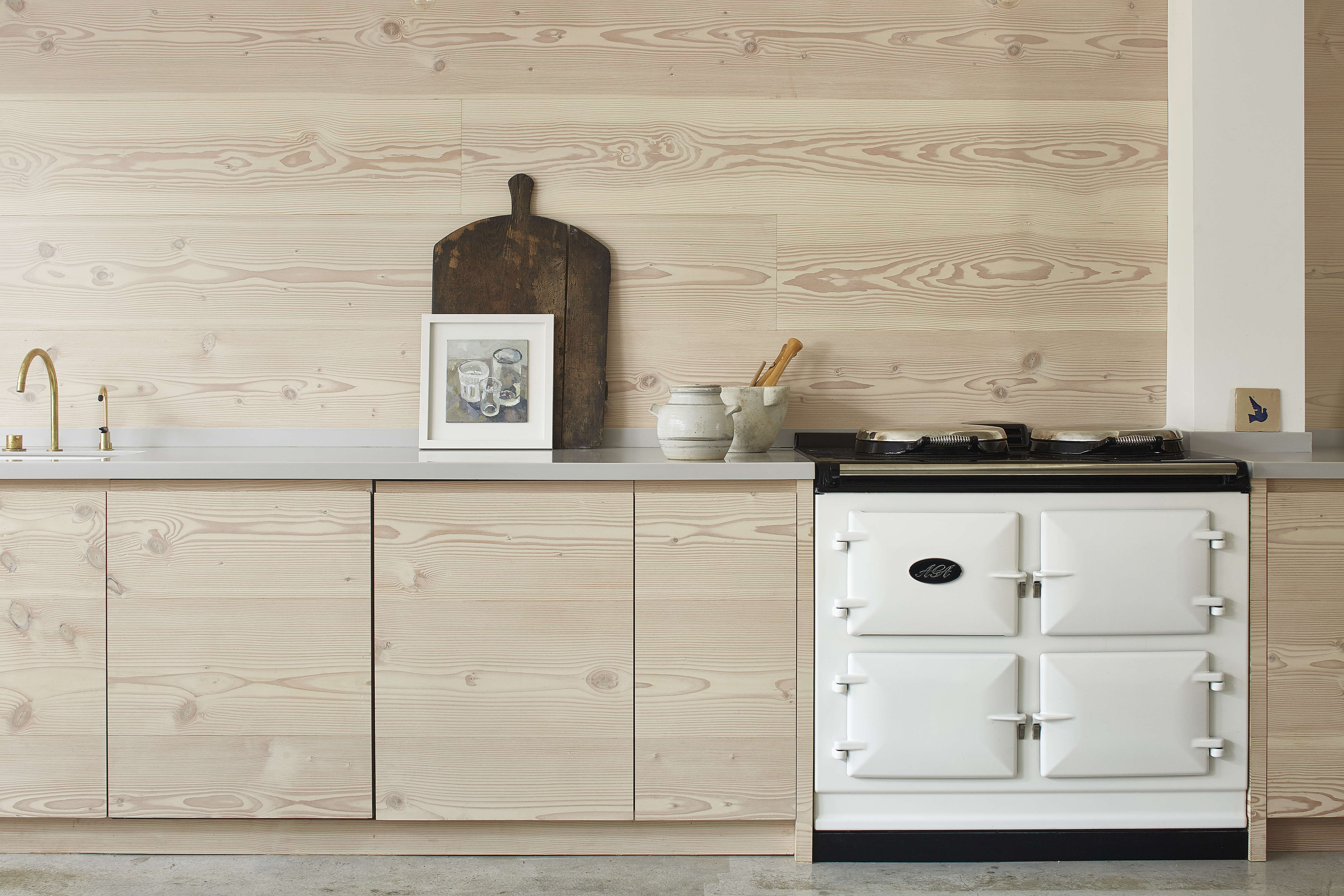 dougls fir cabinets and wall paneling and a white aga in a scandinavian pale wo 10