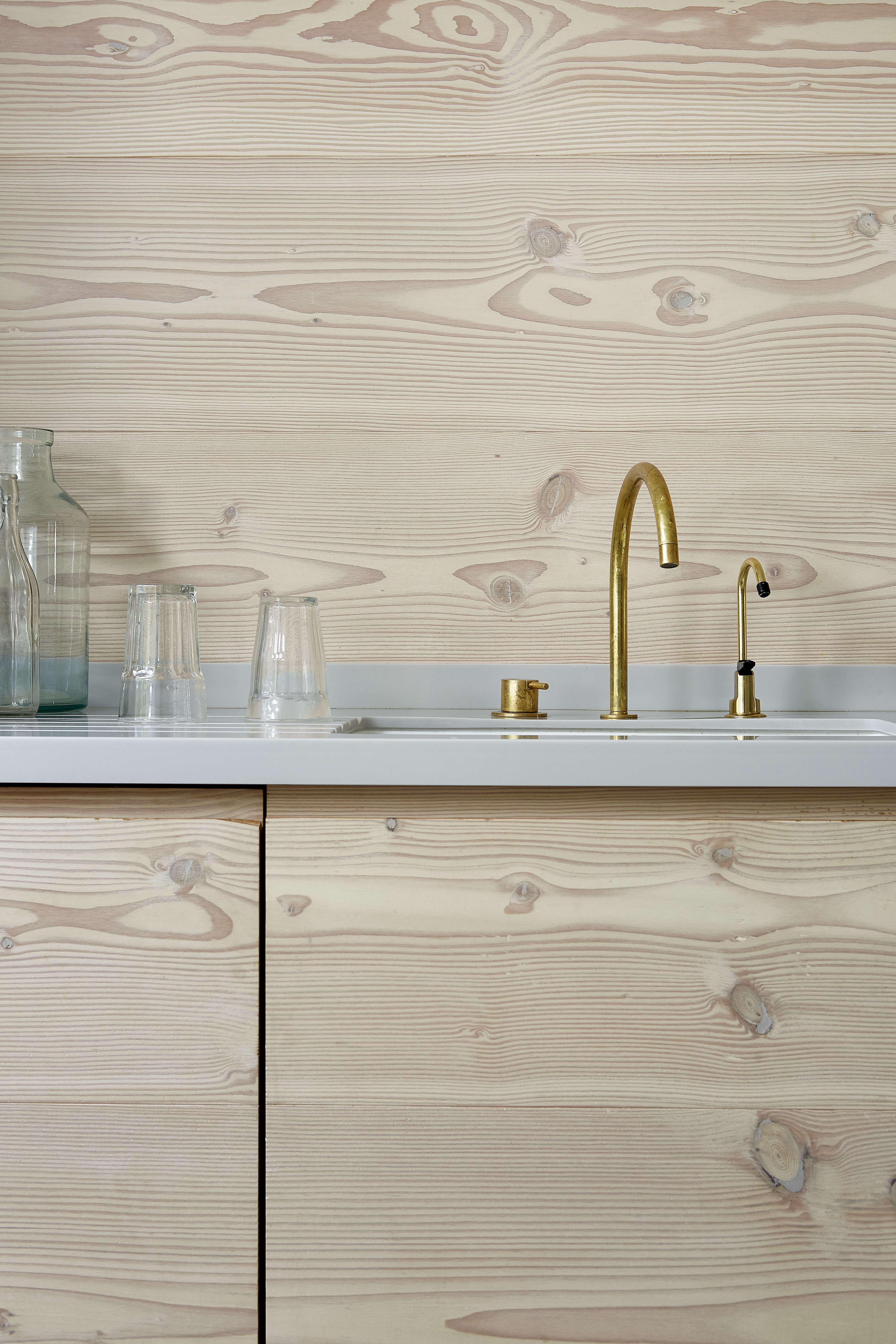 dougls fir cabinets and wall paneling and a brass vola faucet in a scandinavian 11