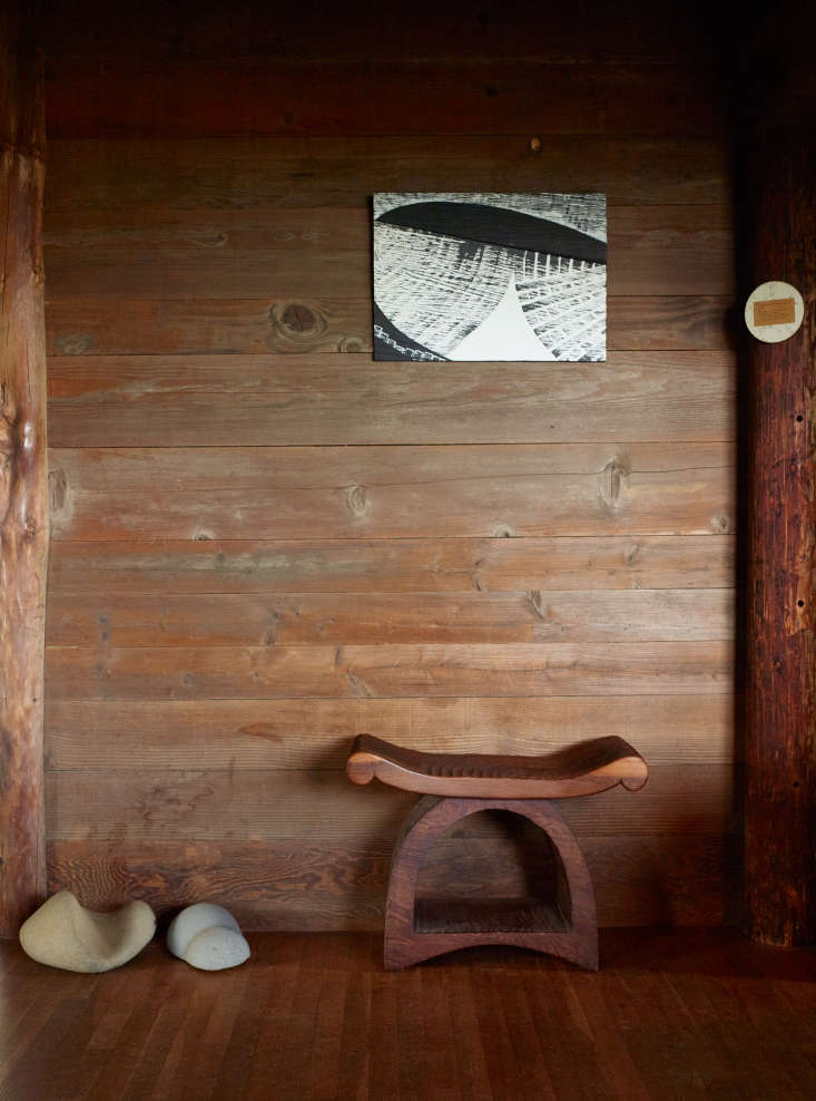 Blunk House Inside a Masters Sculptural Homestead Hewn by Hand in Northern California Blunk's painting in black and white mirrors the chainsaw markings on the underlying redwood plank. The flared and curved outlines of the redwood stool echo the silhouettes on a display of river rocks.