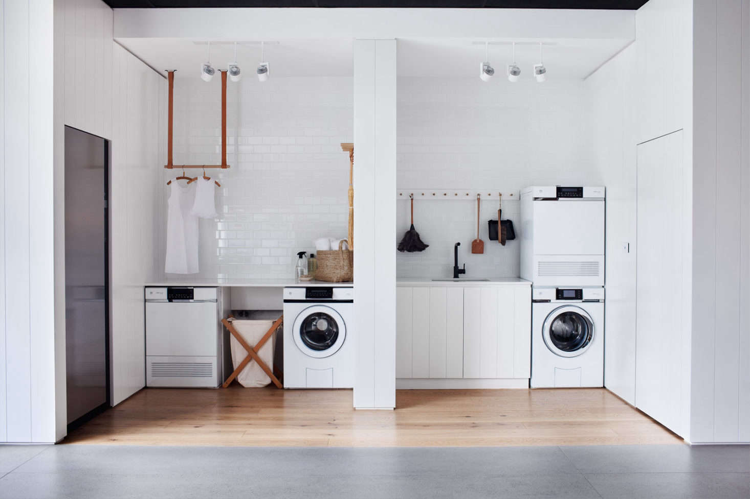 On the left side of a showroom, a washer and dryer are installed side by side; at right, the units are stacked. See Steal This Look: All-White Laundry Room in Melbourne for more.