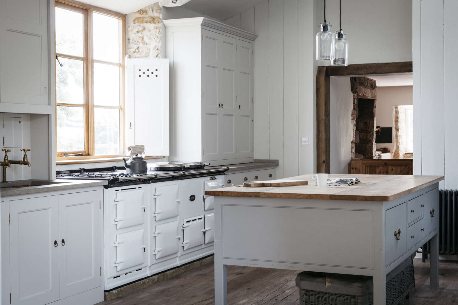 A modern spin on a classic English kitchen in a Dorset farmohuse by Plain English, white Aga included