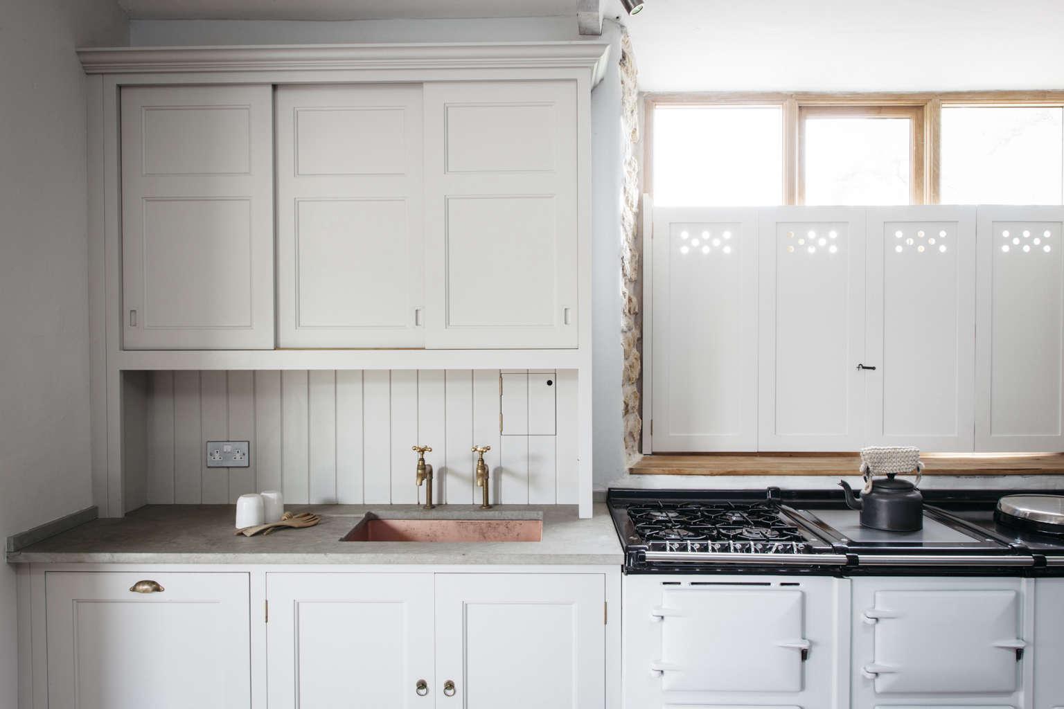 Pierced wood interior shutters in a Dorset farmhouse kitchen by Plain English