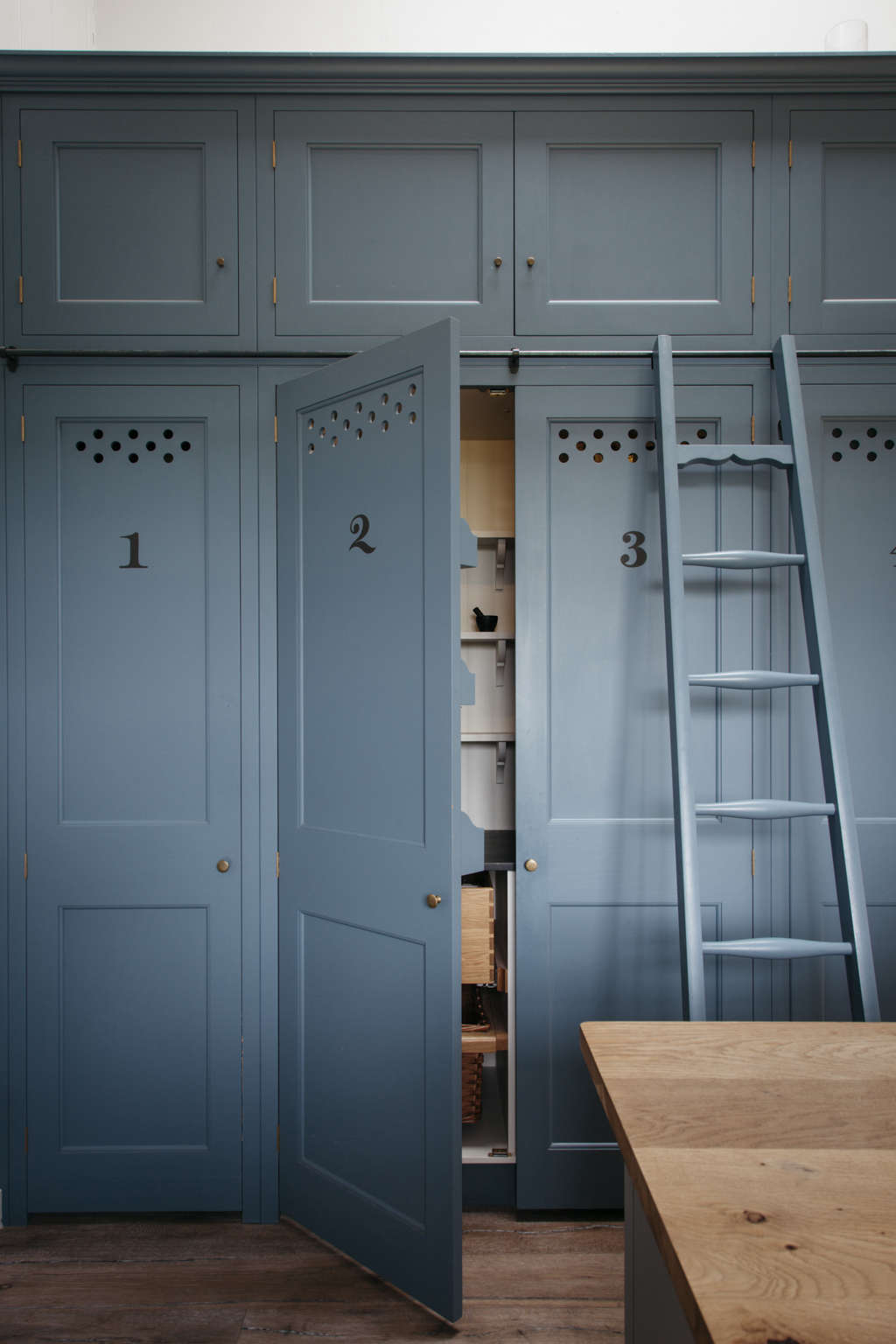 Numbered kitchen cabinets with ventilation holes and a rolling ladder in a Dorset farmhouse kitchen by Plain English