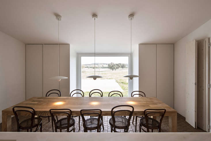 The farmhouse table is surrounded by a suite ofvintage Era Chairs by Michael Thonet and lit with a trio of Davide Groppi Ovonelpiatto Lights.