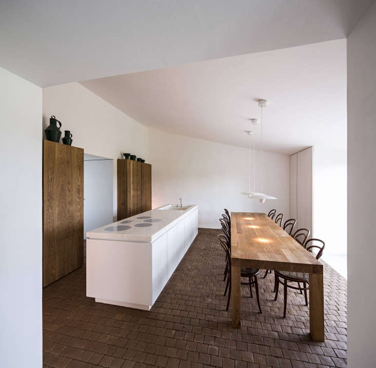 A wall of kitchen storage and appliances is located behind a marble-topped kitchen island.