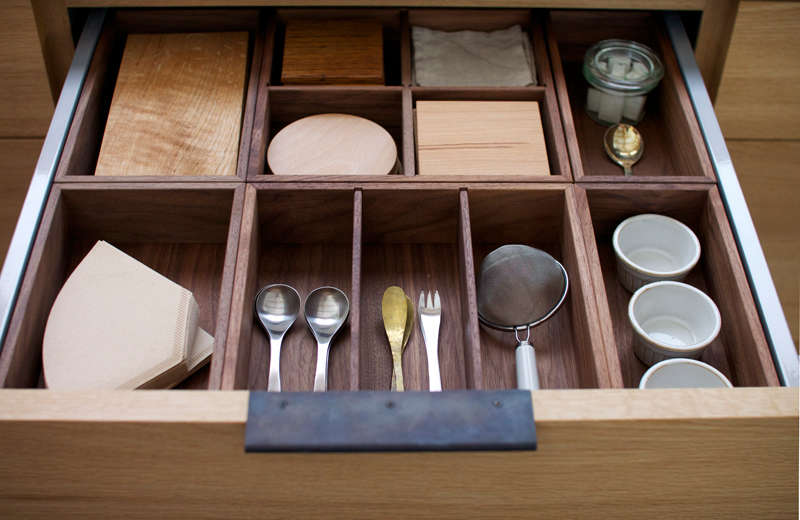 Snedker uses handmade wood boxes as drawer organizers; they can be lifted out and used as trays.