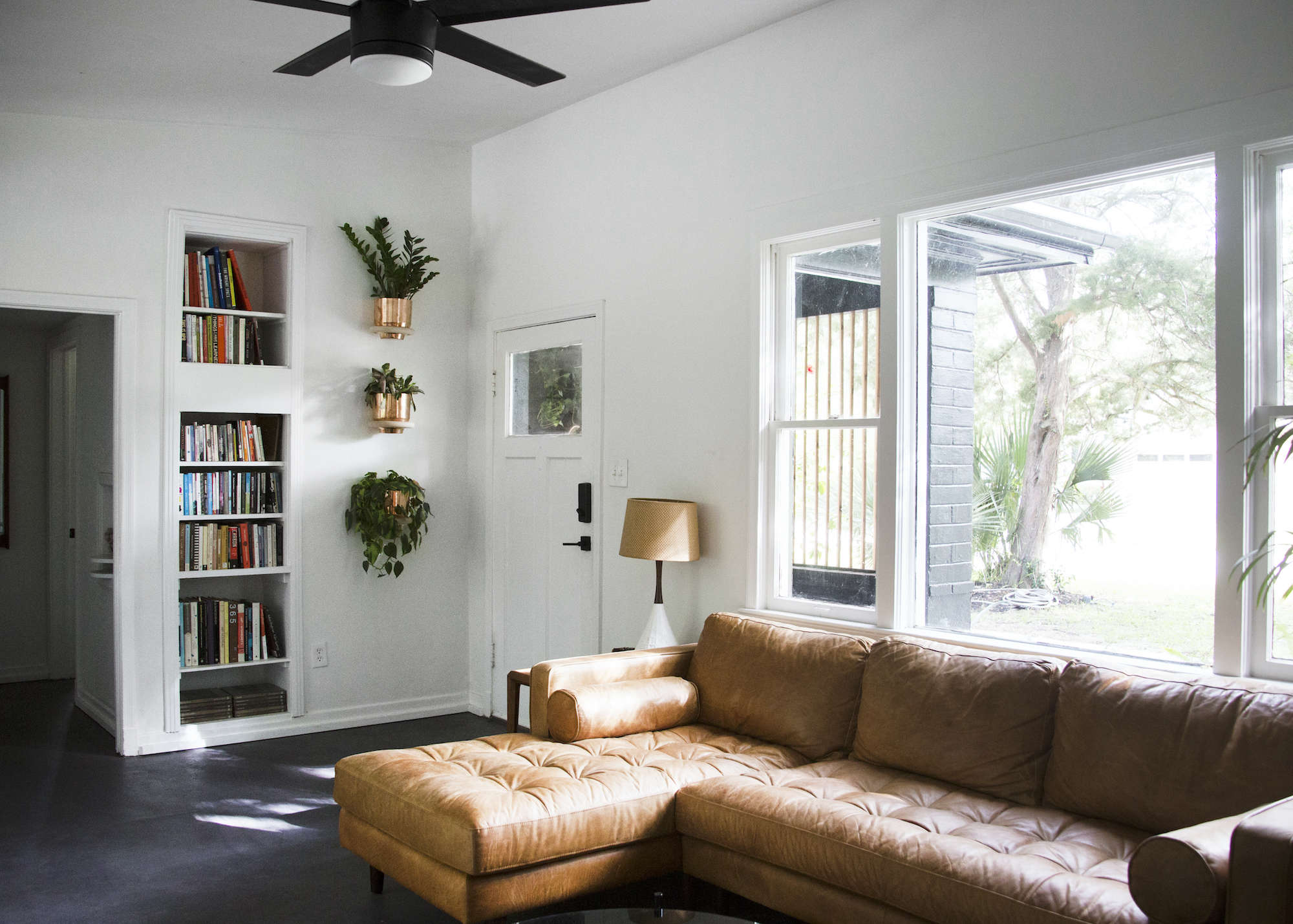 living-room-brown-leather-couch-plants-copper-pots