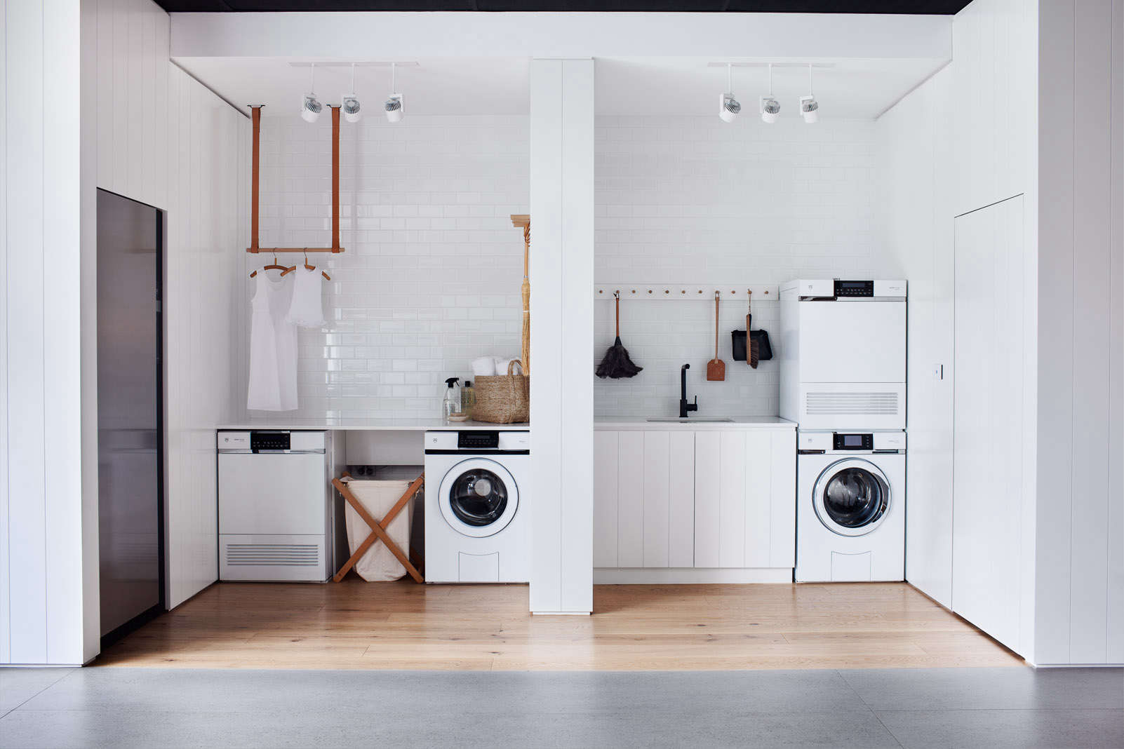 A ceiling-mounted drying rack and Shaker peg rail conserve spacein an appliance showroom in Australia; seeSteal This Look: All-White Laundry Room in Melbourne.