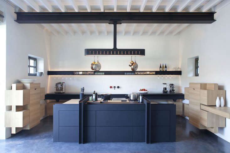 The kitchen at Château de La Resle, a hotel in Burgundy, France, is designed in oak with a blue powder-coated steel work table.