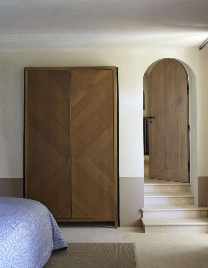 In another bedroom, a freestanding stained oak wardrobe is set in a wall niche.