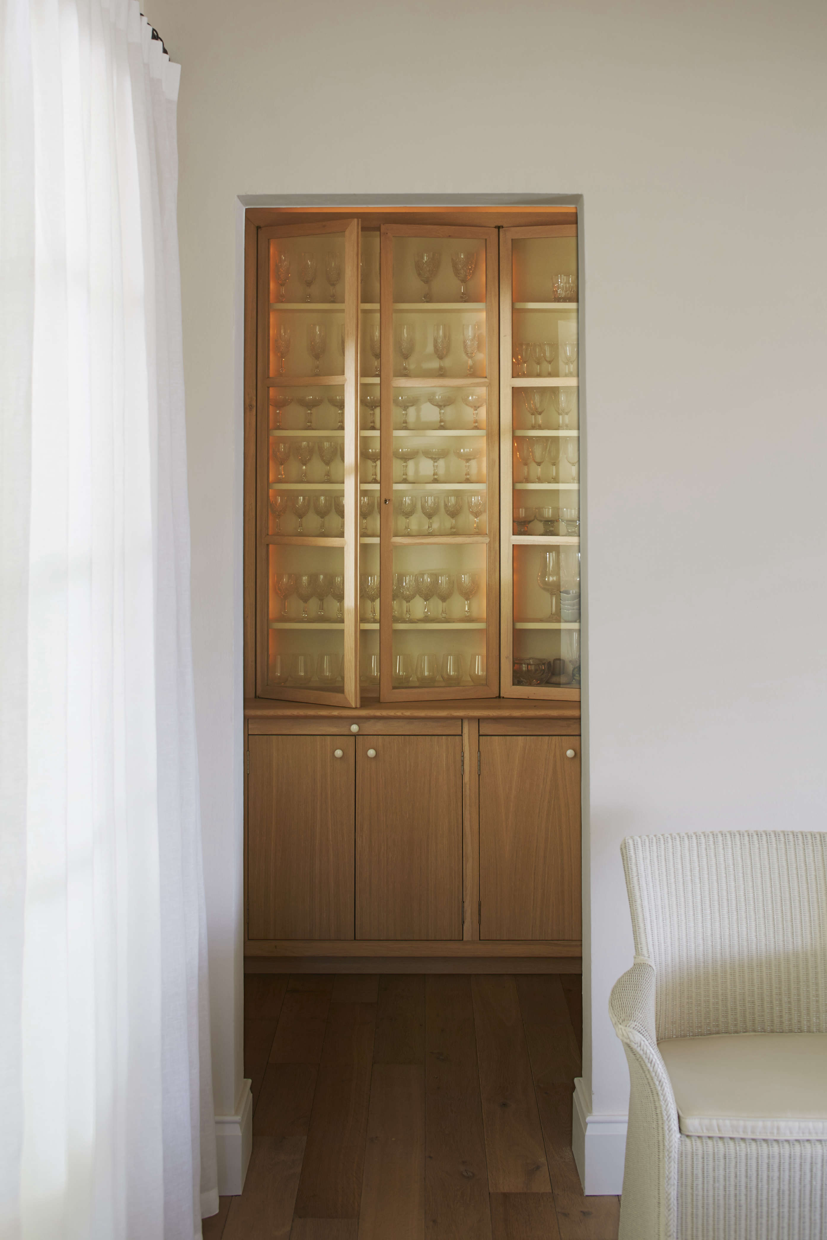 Bar storage is conveniently right off the dining room in a built-in china cupboard. The floor is wide-plank oak.