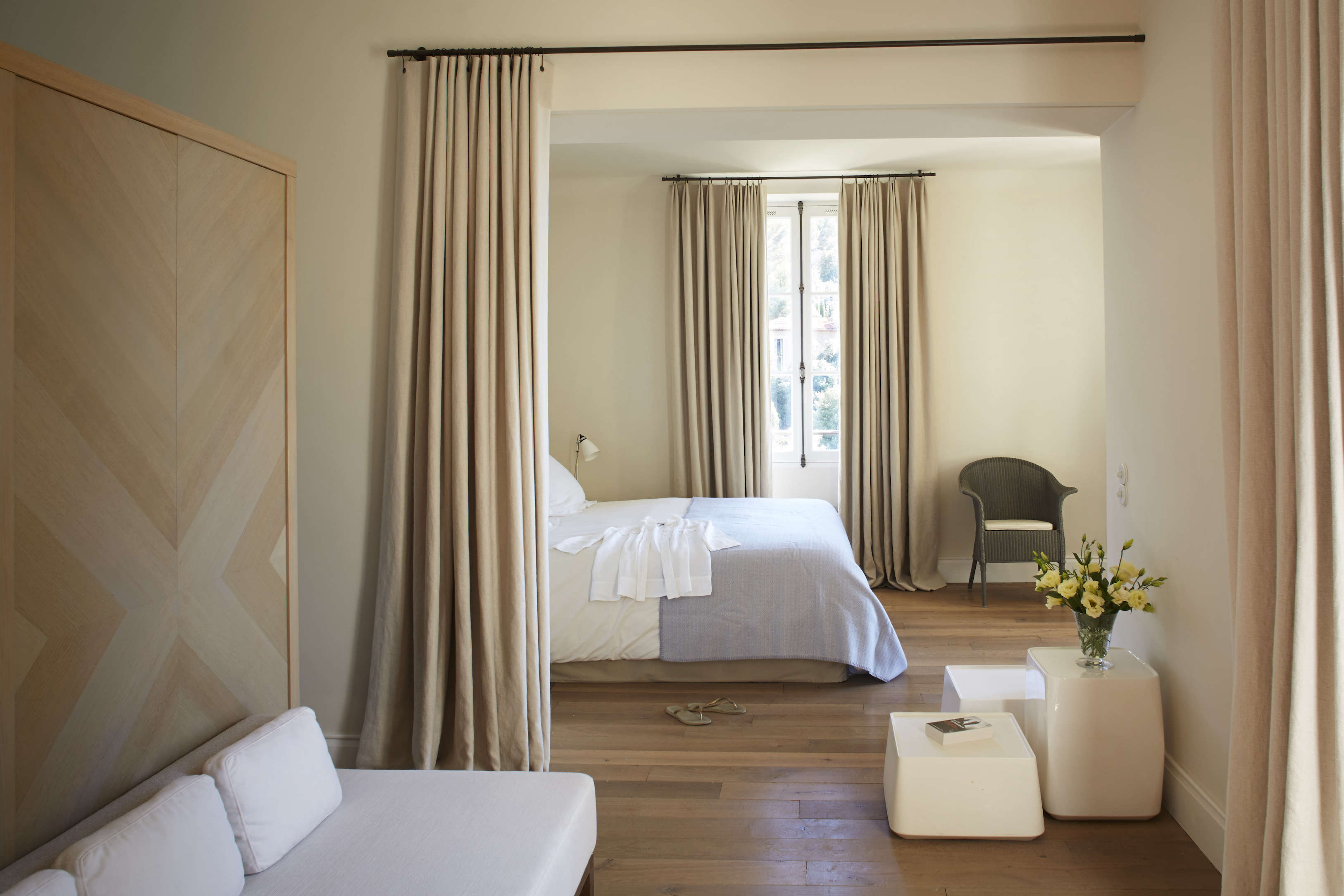 The master suite has a sitting area with a meridiènne, a low sofa that stands against a stained oak wardrobe.
