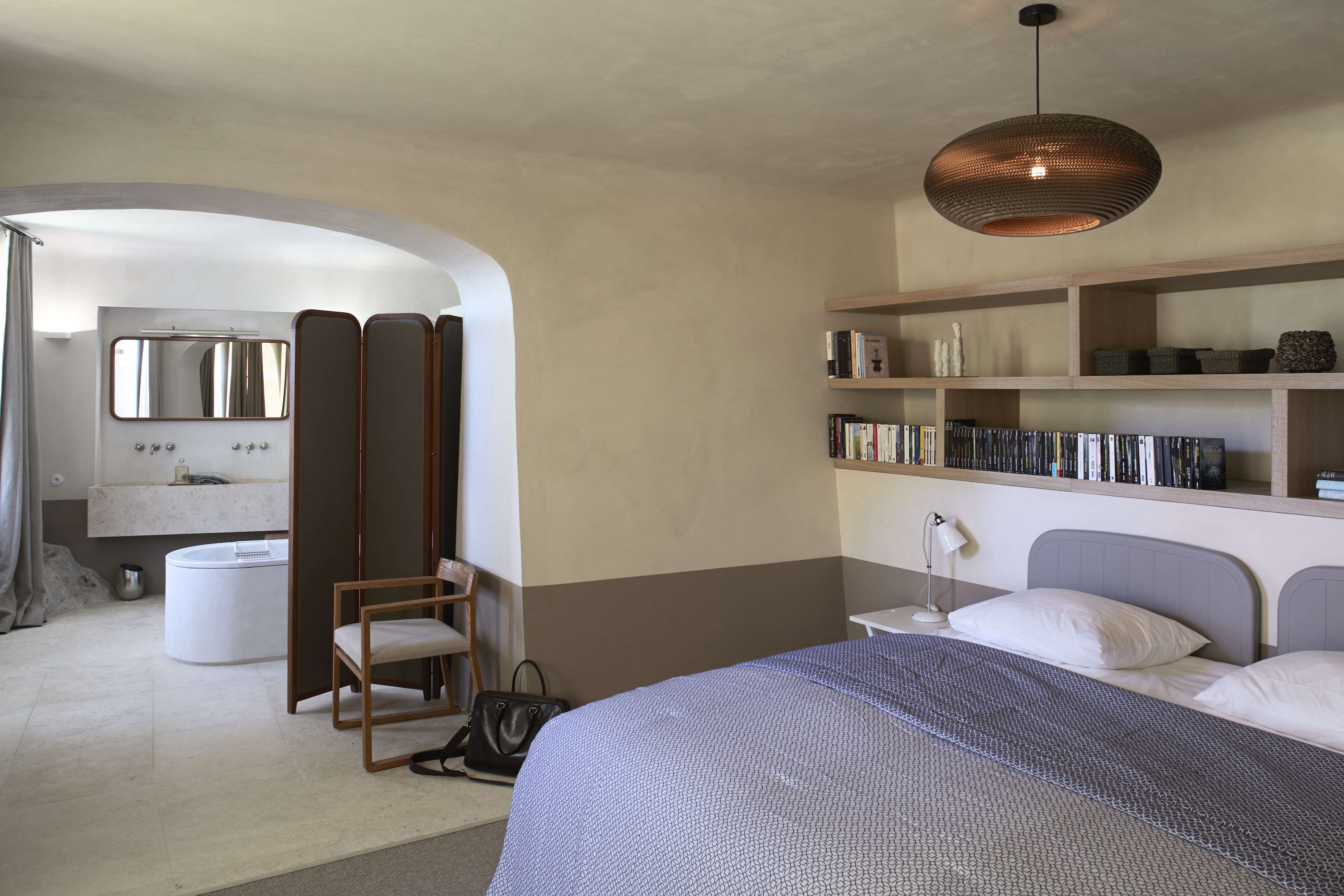 The guest room has an en suite bath divided by an archway and folding screen. The painted pine double headboard, Barnes tells us, was &#8
