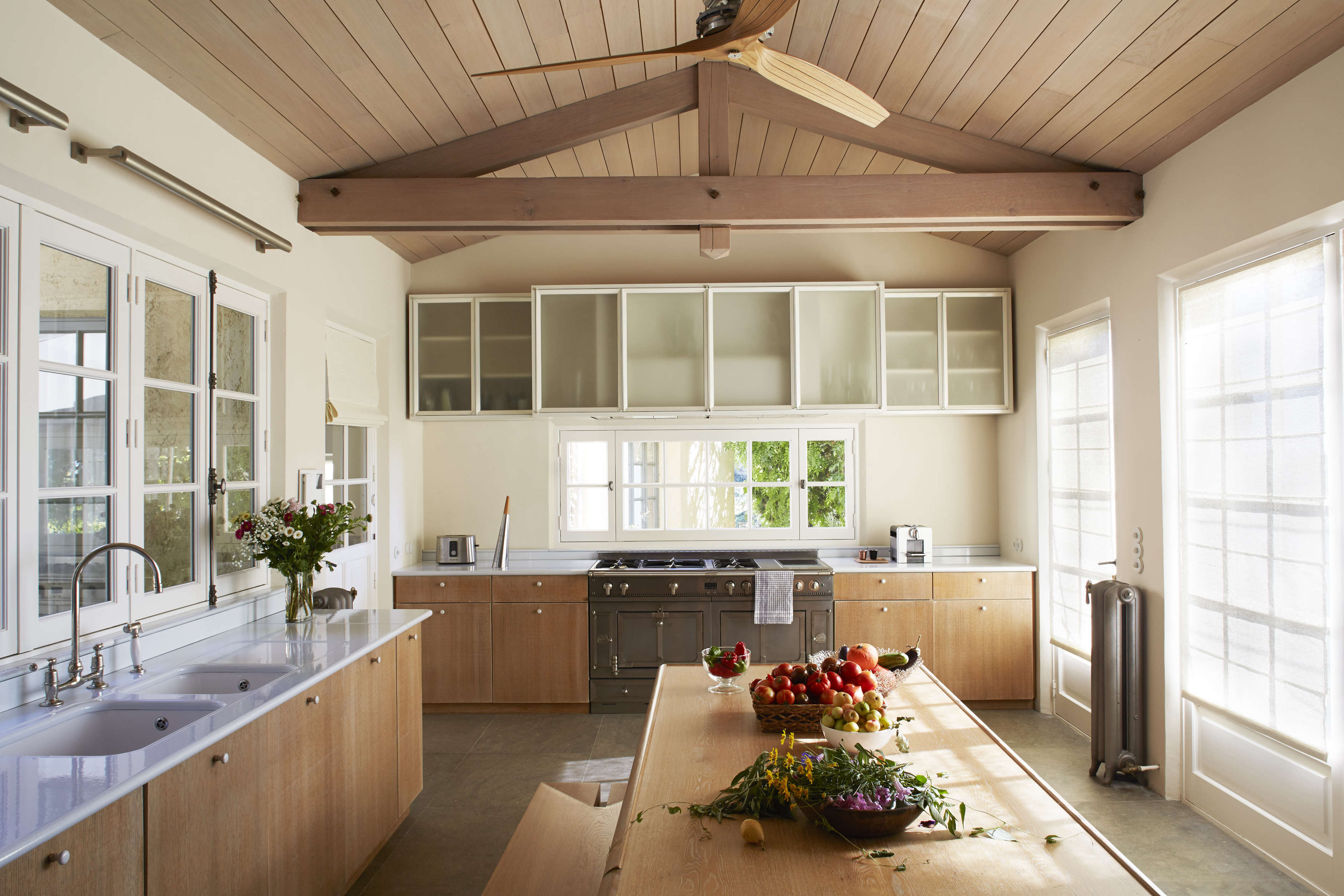 Envisioning the vacationing owners and their friends gathering in the kitchen, Barnes created a refined-rustic look by inserting solid oakbeams and a paneled oak ceiling.