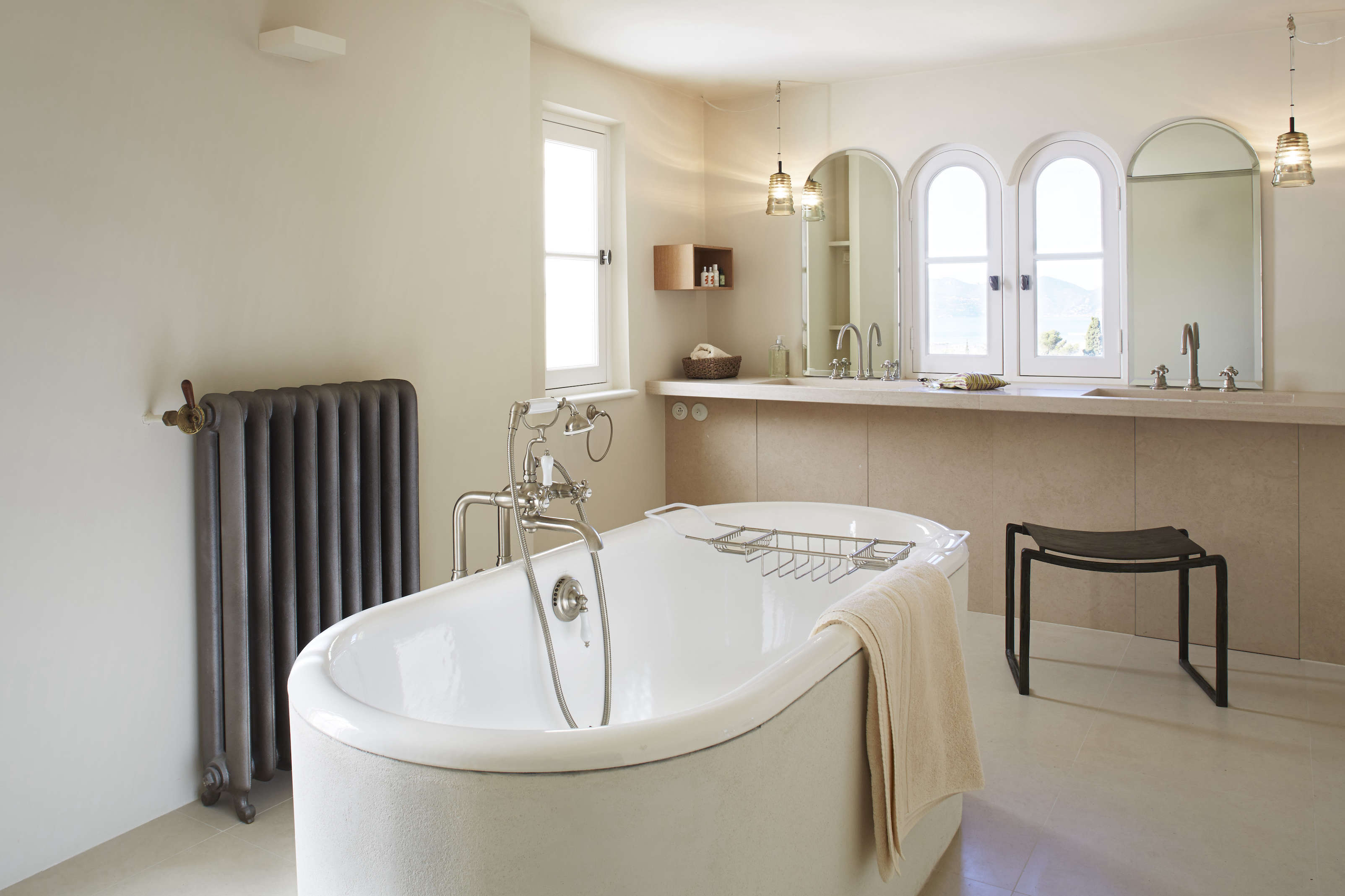The master bathroom features a freestanding oval bathtub from Bette and double sinks with mirrors that echo the arched windows. The metal radiator is from Alphamétal, a French company that specializes in renovating (and also reissuing) classic cast-iron radiators.