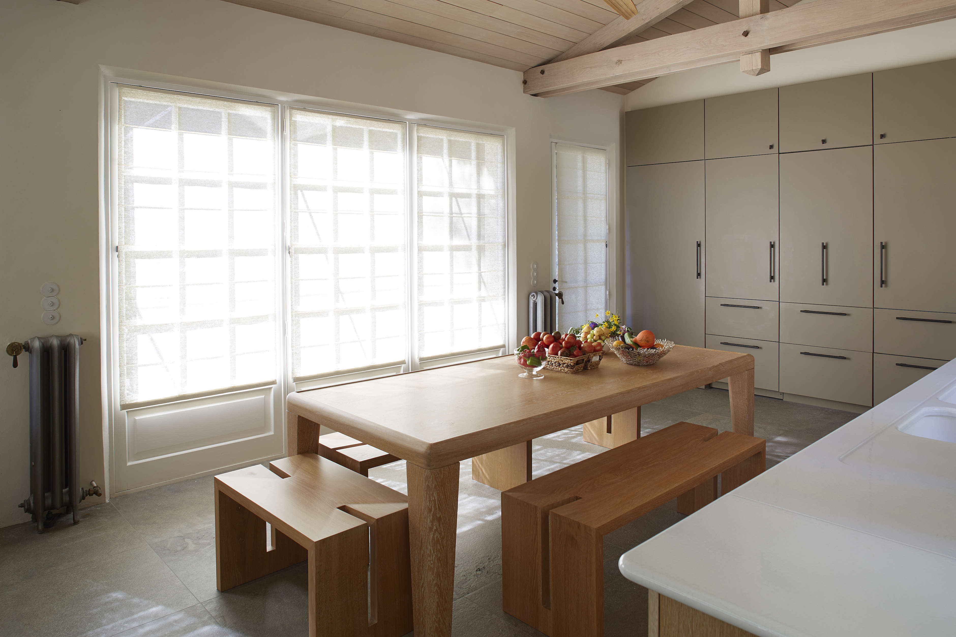 The kitchen has a minimalist table and benches that are signature EBI designs made in France. The wall of built-in storage incorporates the fridge and freezer and the door to the laundry. The floor is a mottled gray stone from Cascais, Portugal.