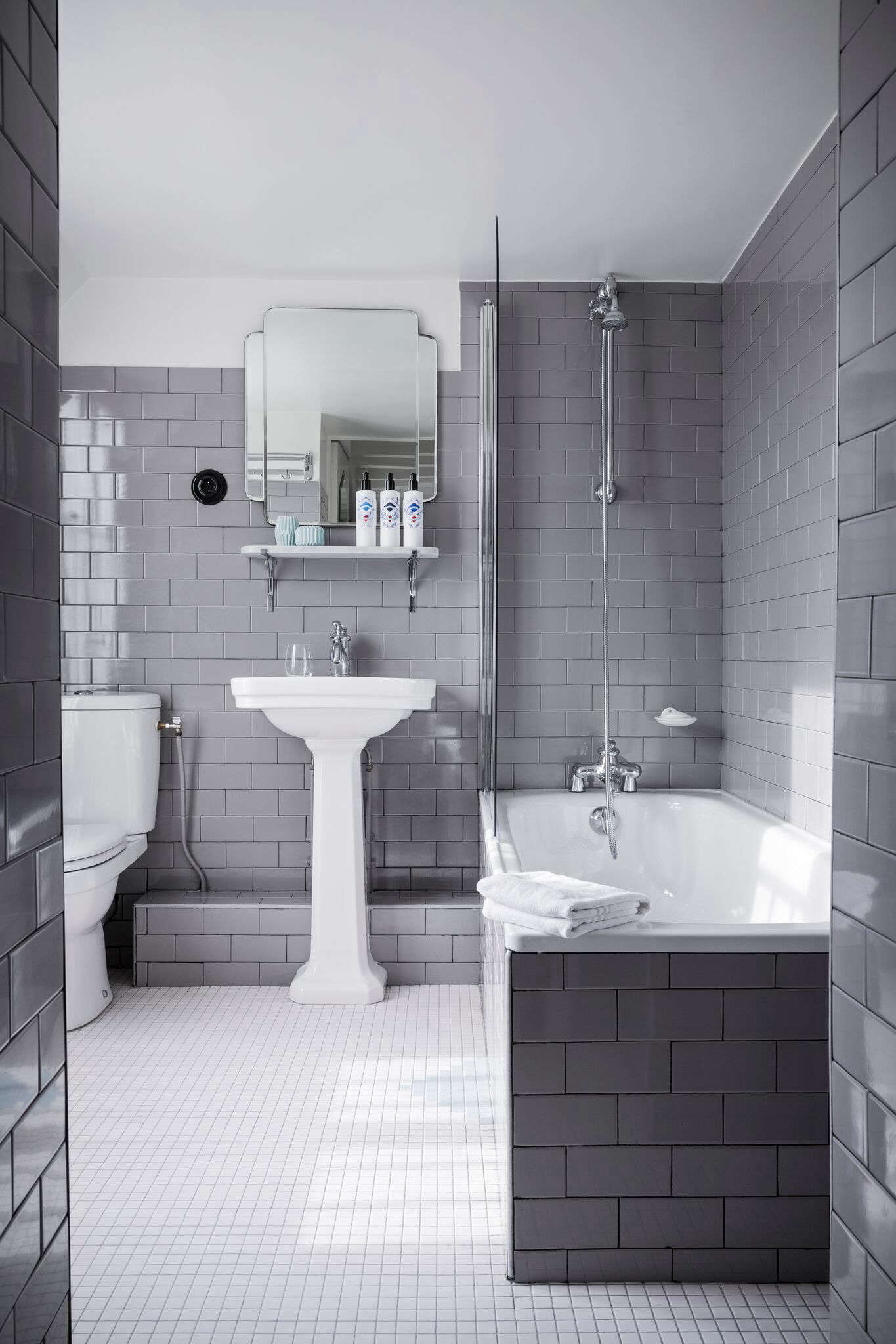 Far from outdated: a gray-tiled built-in bath (with a glass shower wall) at Hotel Panache in Paris; see Hotel Panache: The Power of Jolie Laide Style for more.