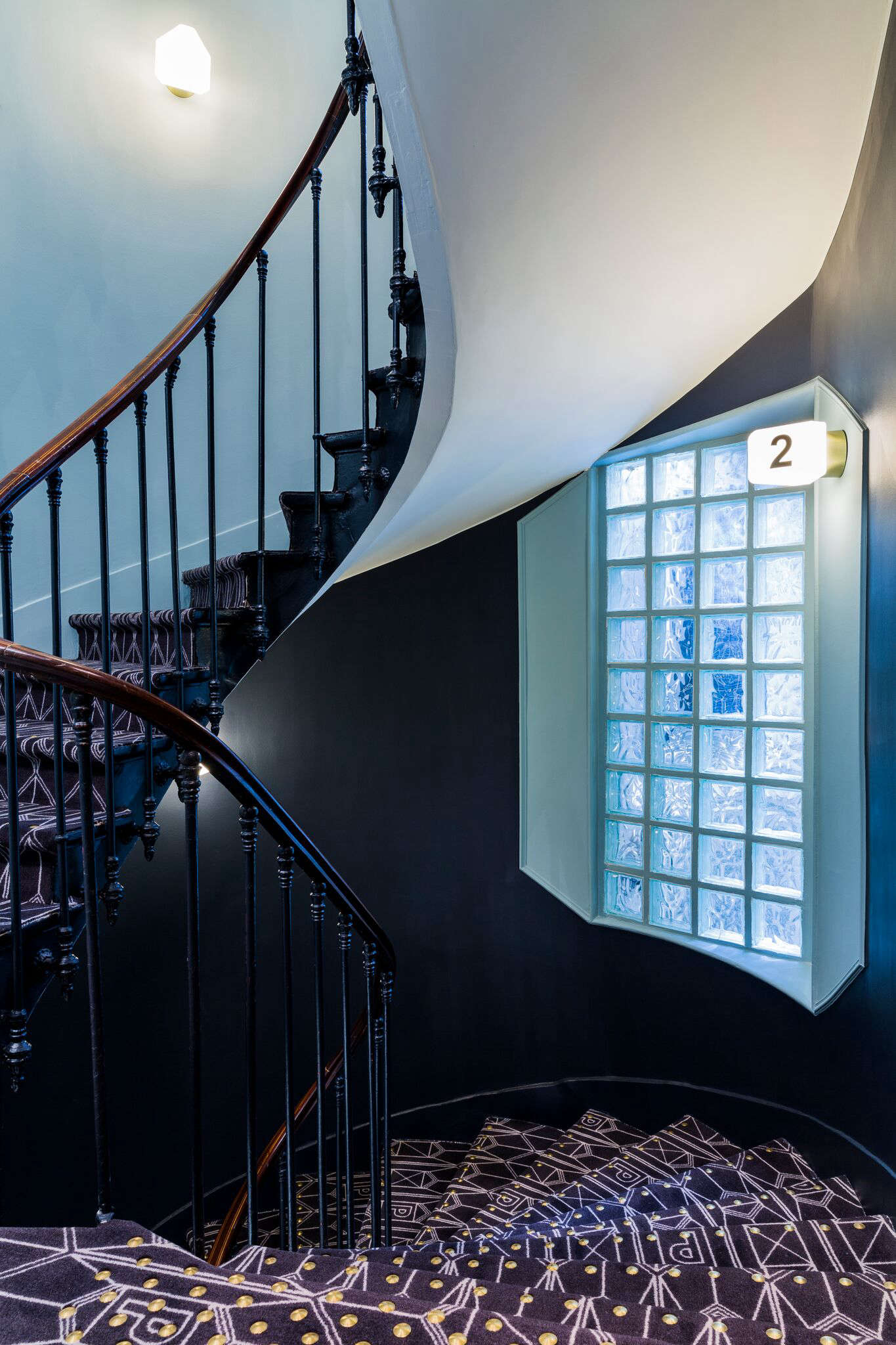 The hotel has seven floors. The winding stair is carpeted in a custom pattern inspired by old coats of arms.