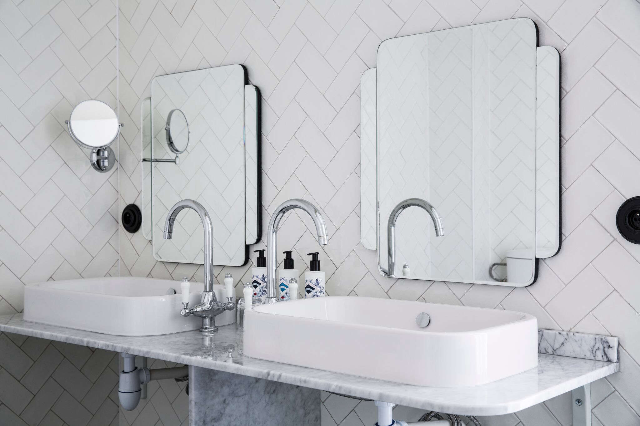 In a suite, a two-person sink in a minimalist marble vanity set off by herringbone-patterned subway tiles. For shaped mirrors, see Pottery Barn&#8