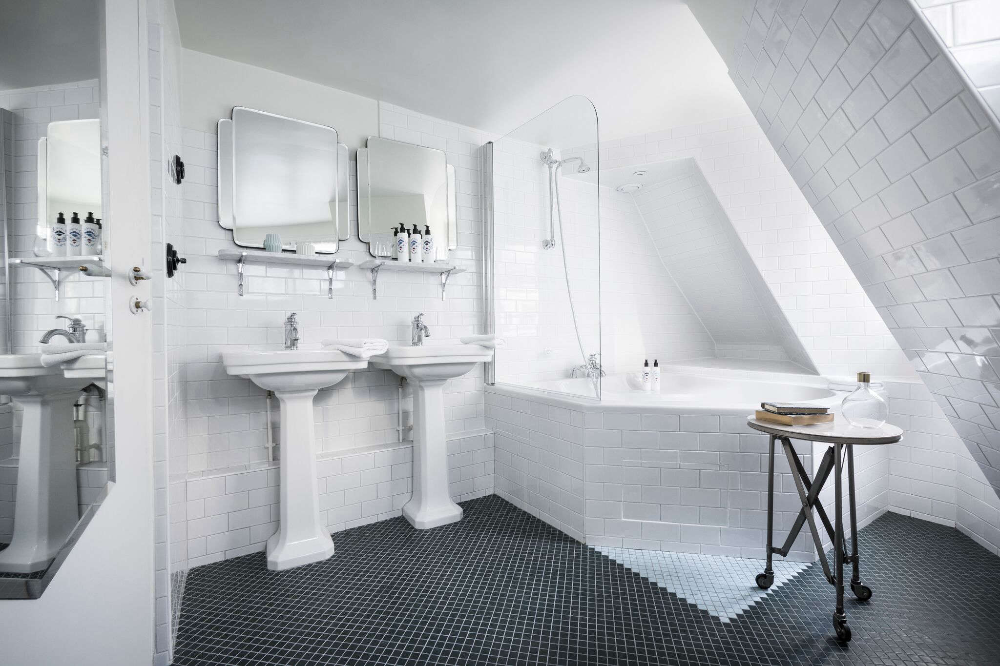 Meilichzon told us she sourced the pedestal sinks from Imperial and Kohler and the mirrors from Objet de Curiosité. She used stacked subway tile on the walls and tub and playfully planted a white tile triangle on the black-tiled floor.