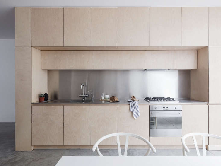 The clean-lined kitchen is birch plywood finished with a water-based acrylic varnish. The stove is a Smeg and a full-size fridge is located to the right of it.