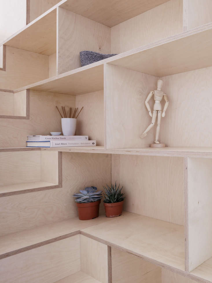 The shelving elegantly wraps aroundthe stairs and the plywood seams are left exposed.