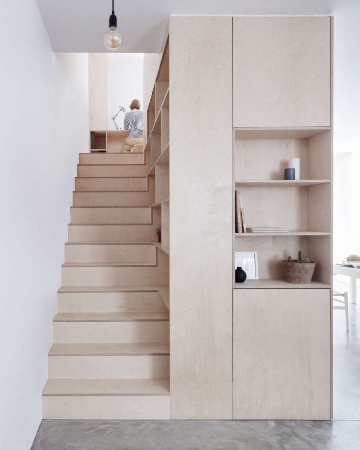 Plywood stairs (and built-in shelving) in A London Townhouse Designed to Catch the Light. Photograph by Rory Gardiner.