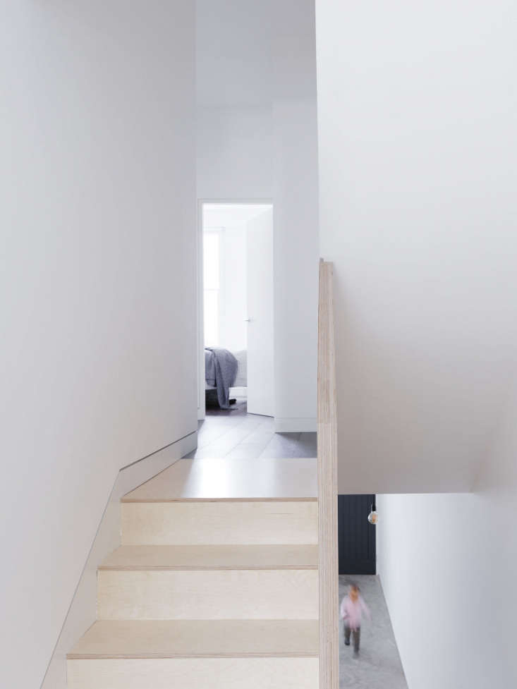A partition of double-width plywood serves as the stair rail. The upper level has dark wood floors.