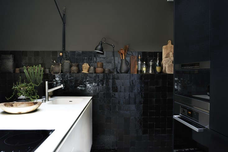 A black-and-white kitchen in Lyon, France, designed by Stephane Garotin and Pierre Emmanuel Martin of Maison Hand, features glossy black tiles and bitter chocolate walls. Photograph by Pia Ulinfrom Monochrome Home, Elegant Interiors in Black and White. See Expert Advice: Monochrome for the Minimalist (and Maximalist).