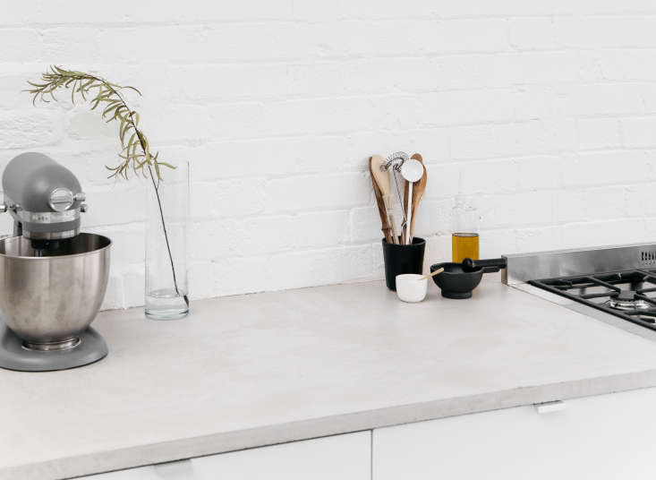 "A kitchen in a huge space in East London has hybrid concrete counters: marine-grade MDF plastered with a thin layer of micro-concrete. ""We wanted to use normal concrete, which is more water-resistant, but it's too heavy; micro-concrete isn't water-resistant,&#8"
