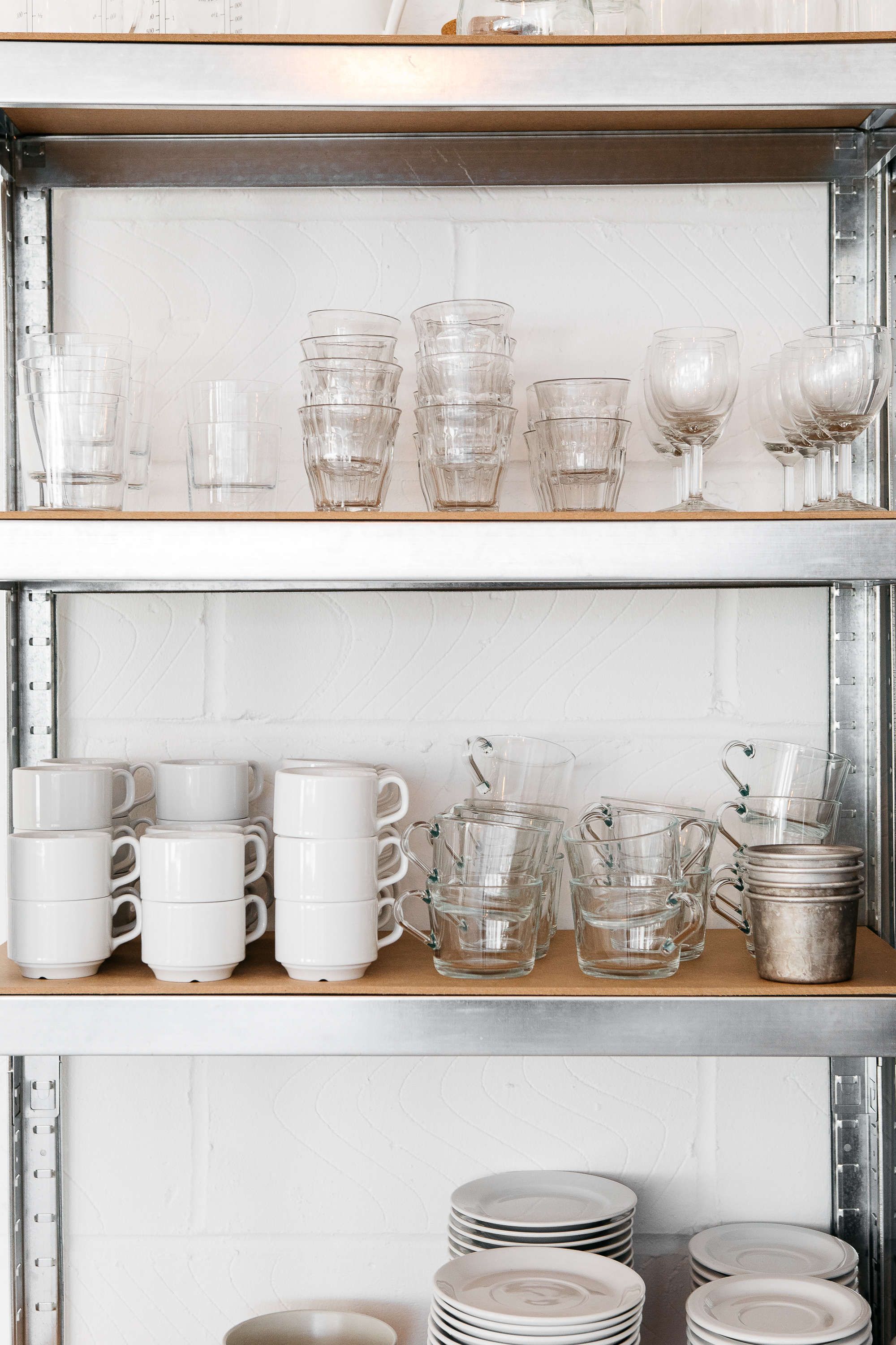 clear glass tumblers and white ceramic teacups and saucers on stainless steel i 22