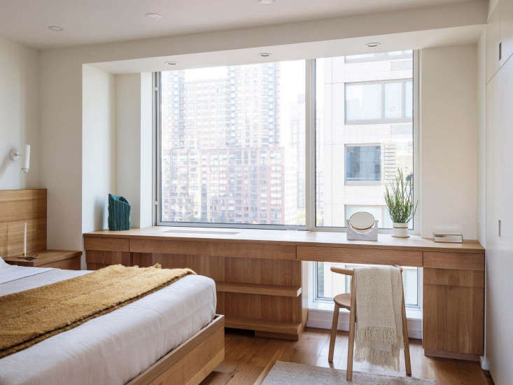 In a compact apartment by New York-based Workstead, custom oak millwork creates a desk/vanity, clothes storage, and countertop, all in one. Also included: built-in nightstands with drawers. See The Artful Shoebox Apartment, Workstead Edition for more.