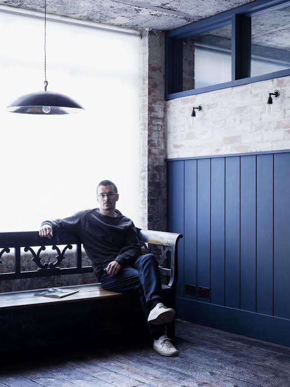 designer mark lewis sits on an antique bench in the office area outside the bed 14
