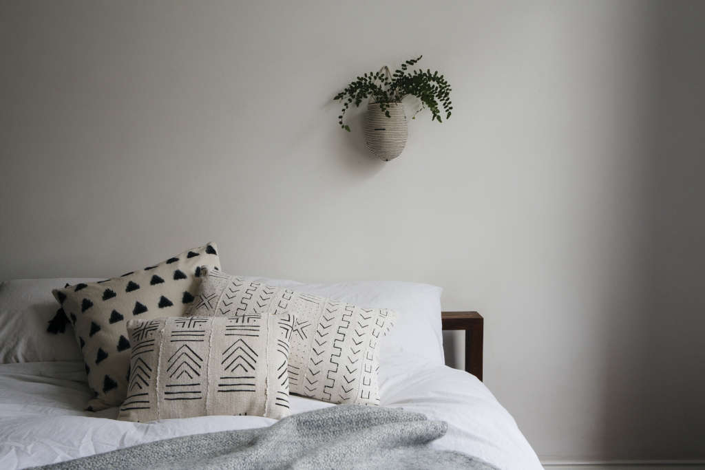 In the master bedroom are examples of Ash's range of mud-cloth cushions. The fabric is made in Mali from strips of vintage fabric that have been sewn together and dyed with fermented leaves and river mud. Each of the designs has a significance in Malian culture. The gray Welsh blanket is also available through her shop.
