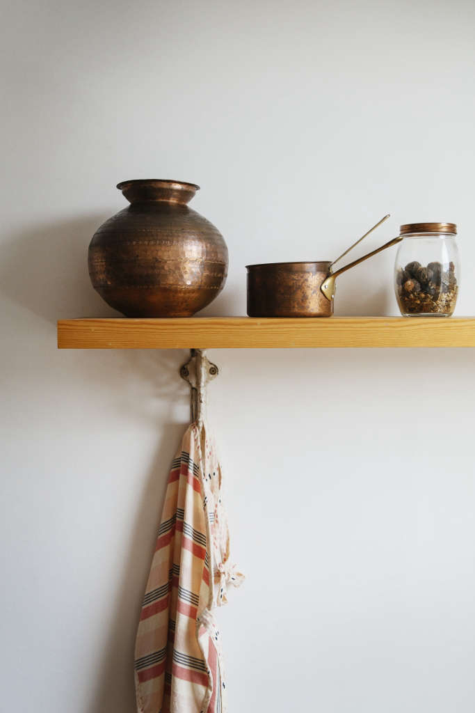 Open shelves hold vintage copper pots; a hook keeps a colorful tea towel at the ready.