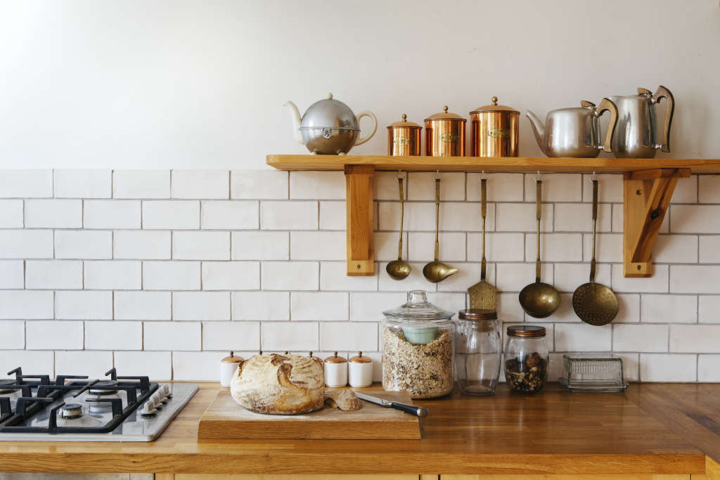 The compact birch-ply kitchen was built by Ash's uncle, a carpenter. The work surface is protected with Danish oil. The vintage metallic kitchen implements were sourced from antique shops in Ashburton in Devon, Ash&#8